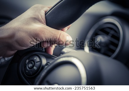 A hand pushes the cruise control button on a steering wheel. #235751563