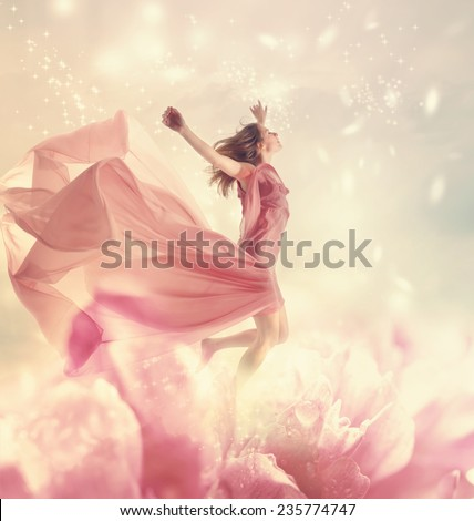 Beautiful young woman jumping on a giant flower #235774747