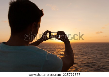 man taking picture of beautiful sunset over sea