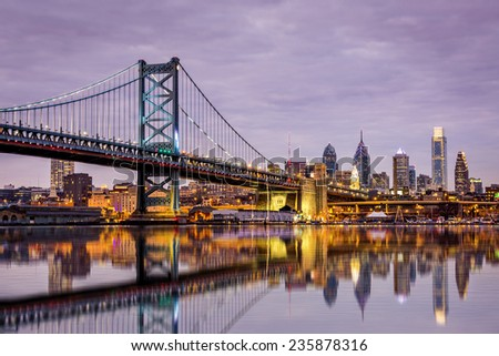 Ben Franklin bridge and Philadelphia skyline reflected in the Delaware river under a purple twilight