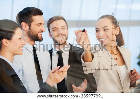Discussing successful business project. Confident young businesswoman drawing a graph on glass and smiling while her colleagues standing near her  #235977991