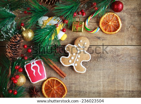 Homemade christmas painted gingerbreads (gingerbread man and red present) on the wooden background with Christmas decorations, cones and candied orange. Selective focus on the man. Toned