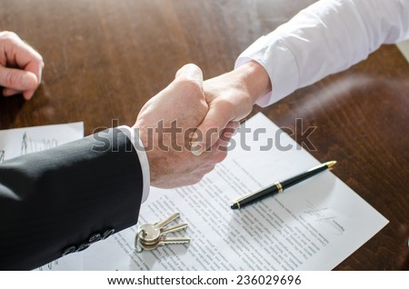 Estate agent shaking hands with his customer after contract signature Royalty-Free Stock Photo #236029696
