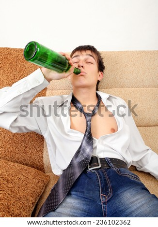 Teenager drinks a Beer on the Sofa at the Home #236102362
