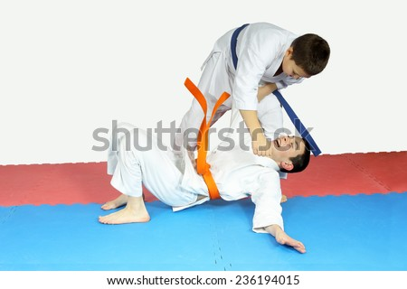 The athlete threw another athlete on the mat and hits him in the chest #236194015