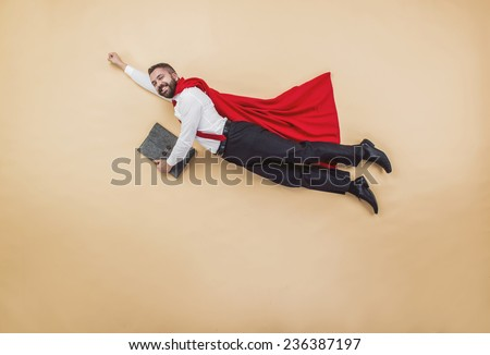 Manager in a superman pose wearing a red cloak. Studio shot on a beige background. #236387197