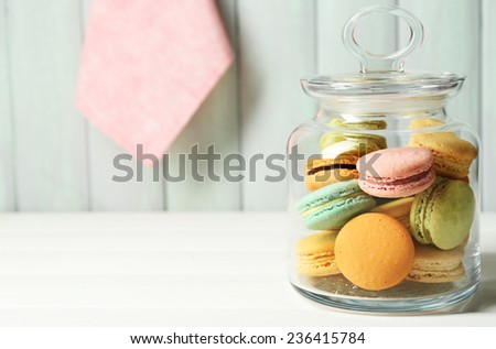 Gentle colorful macaroons in glass jar on color wooden table background #236415784