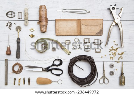 Leather craft tools and utensils on a white wooden background Royalty-Free Stock Photo #236449972
