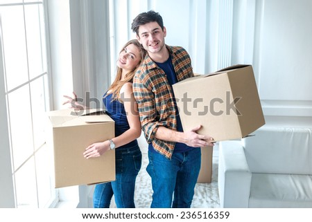 Moving to a new life. A girl and a guy holding boxes for moving the hands and smiling at the camera while a couple in love standing at the window among boxes #236516359