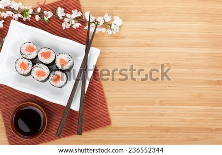 Sushi maki with salmon and sakura branch over bamboo table #236552344