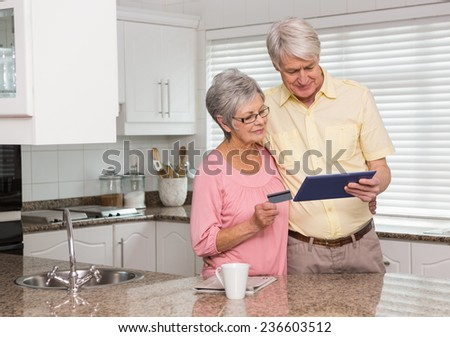 Senior couple shopping online with tablet pc at home in the kitchen #236603512
