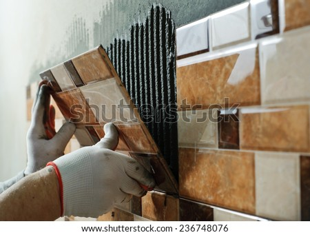 Laying Ceramic Tiles. Tiler placing ceramic wall tile in position over adhesive Royalty-Free Stock Photo #236748076