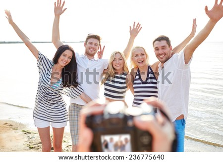 summer, sea, tourism, technology and people concept - group of smiling friends with camera on beach waving hands and photographing #236775640