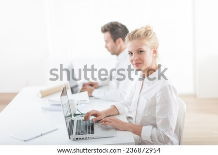 Beautiful businesswoman and her colleague working on computers during a meeting #236872954