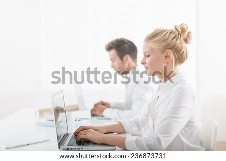 Beautiful businesswoman and her colleague working on computers at office #236873731