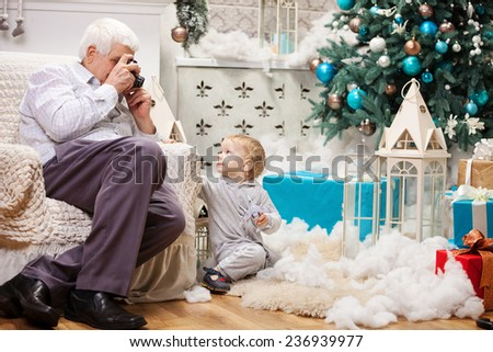 Senior man taking photo of his toddler grandson while sitting near Christmas tree at home