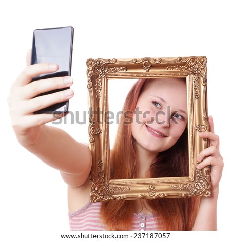 young woman taking selfie with picture frame with camera phone