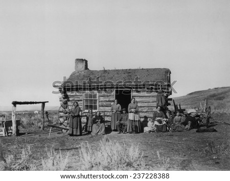 Mormon Family one adult man five adult women and four children in front of their small log cabin in the Great Salt Lake Valley. #237228388