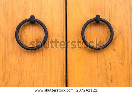 Two Door Knobs of Simple Rings Made of Black Iron  on Yellow Wooden Door of Chinese Style.