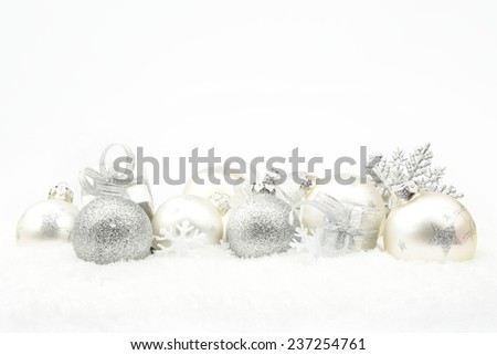 Decoration of silver christmas baubles and gifts in line on snow white background #237254761