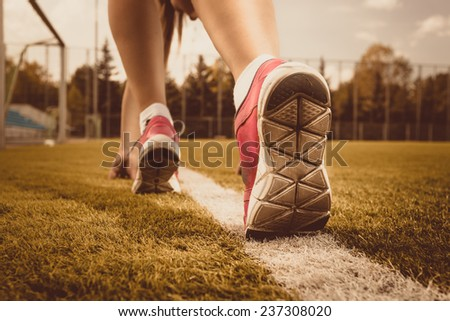 Toned photo of slim woman running on grass field