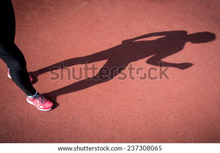 Conceptual photo of shadow of running woman on running track