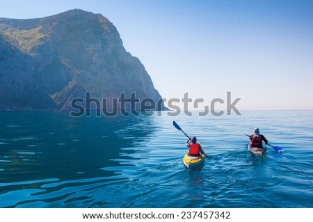 Kayaking in the sea from back view . Royalty-Free Stock Photo #237457342