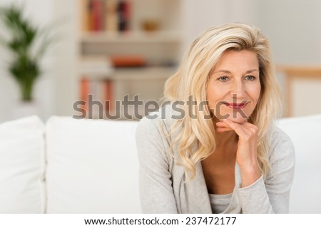 Smiling attractive woman sitting thinking on a sofa at home with her chin resting on her hand staring off to the side of the camera #237472177