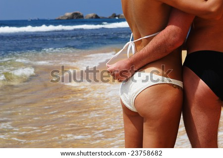 Young suntanned man and the woman in bathing suits embrace on an ocean coast #23758682