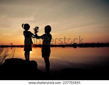 Little girl give a flower to little boy, Silhouette concept