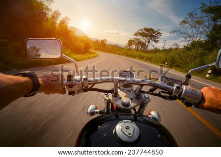 Driver riding motorcycle on the empty asphalt road #237744850