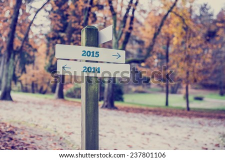 Signpost in a forested area with arrows pointing two opposite directions towards year 2014 and 2015. Royalty-Free Stock Photo #237801106
