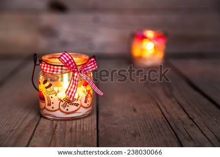 Christmas candle in a glass with drawings of snowmen and snow. Beautiful Burning festive candle tied with a ribbon on an old vintage background