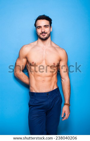smiling shirtless man with beard on blue background #238040206