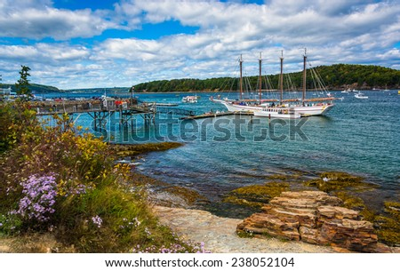 Rocky coast and view of boats in the harbor at Bar Harbor, Maine. Royalty-Free Stock Photo #238052104