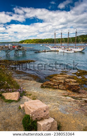 Rocky coast and view of boats in the harbor at Bar Harbor, Maine. #238053364
