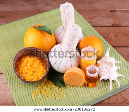 Spa still life with compress balls and coconut shells on color bamboo mat and wooden background #238136272