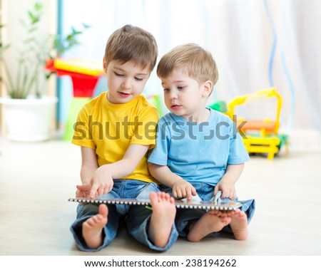 Two kids boys sitting beside him and read a book
