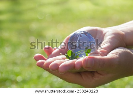 Two hands holding glass globe outdoor, concept for environment protection #238243228