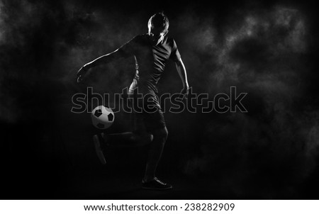 bright soccer playerl on the black background Royalty-Free Stock Photo #238282909