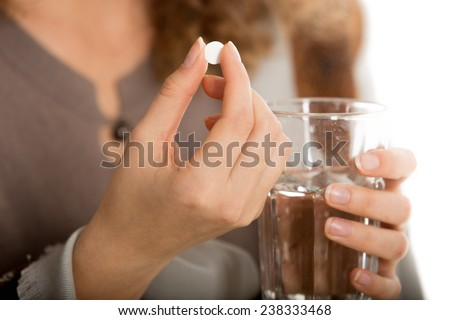 Female hands hold one pill and glass of water close-up #238333468