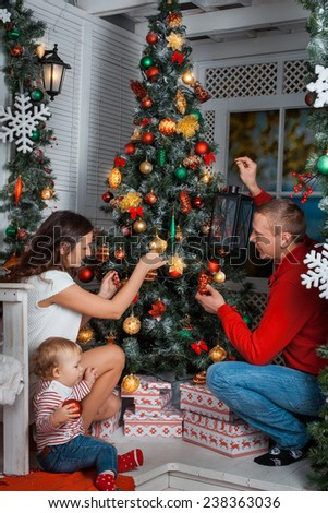 Family with little baby girl decorates the Christmas tree #238363036