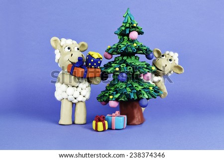 Clay sheep with gifts are playing near Chrismas tree