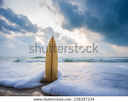 Surfboard on the beach at sunset #238387234