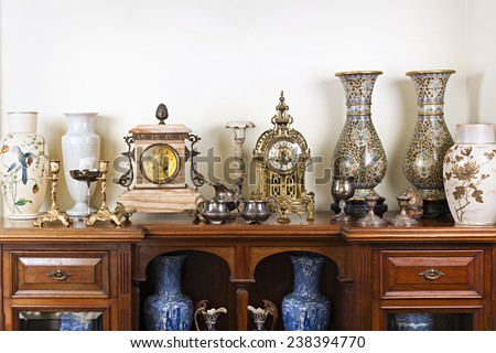 Various antique clocks vases and candlesticks on display Royalty-Free Stock Photo #238394770