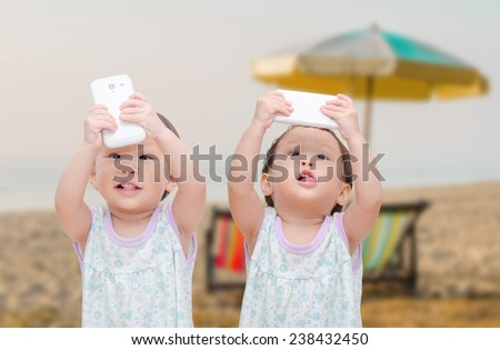 Two little girls and twins taking selfie with mobile phone