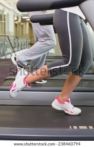 Side view low section of a fit couple running on treadmills at the gym #238460794