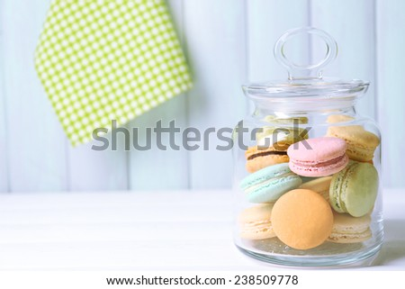 Gentle colorful macaroons in glass jar on color wooden table background #238509778
