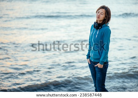 Young woman with big headphones walking on coast and enjoying view of sea #238587448