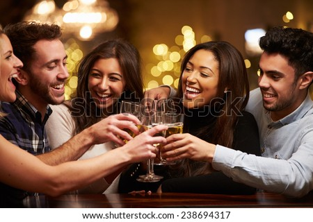 Group Of Friends Enjoying Evening Drinks In Bar Royalty-Free Stock Photo #238694317